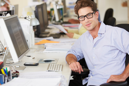 Man Working At Desk In Busy Creative Office