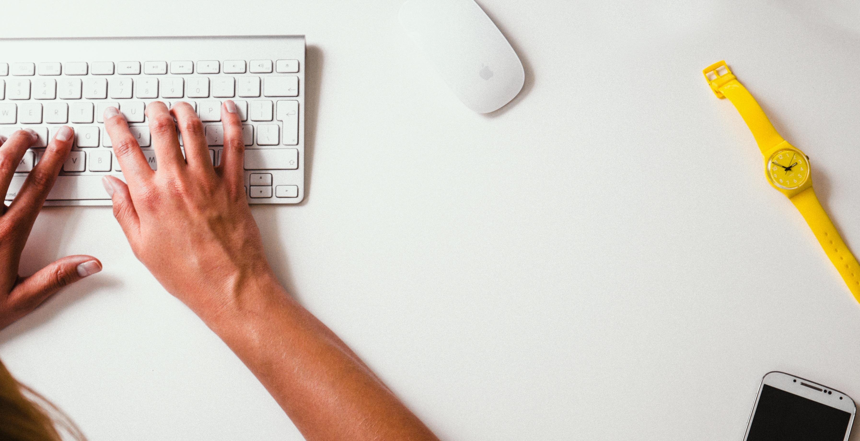 Hände auf Tastatur, darum liegen Maus und Uhr