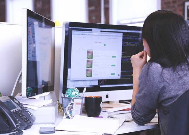 Frau vor zwei Bildschirmen auf Arbeit