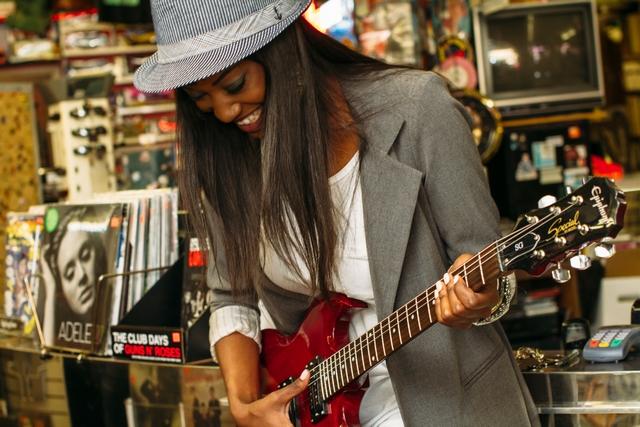das ist eine frau die gitarre spielt und dabei spaß hat
