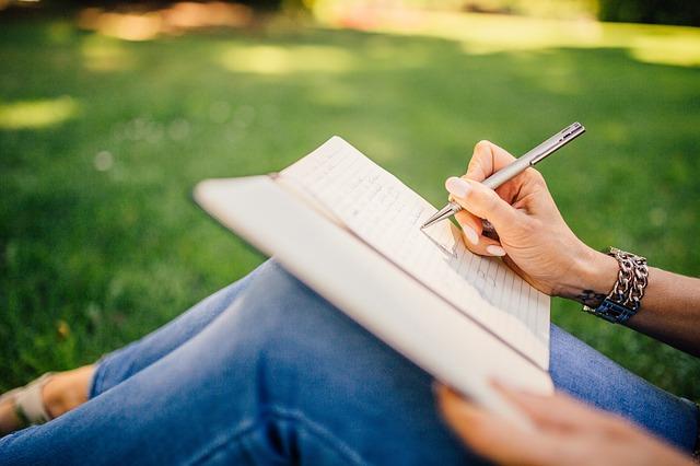 Frau schreibt auf einer Wiese in ein Buch
