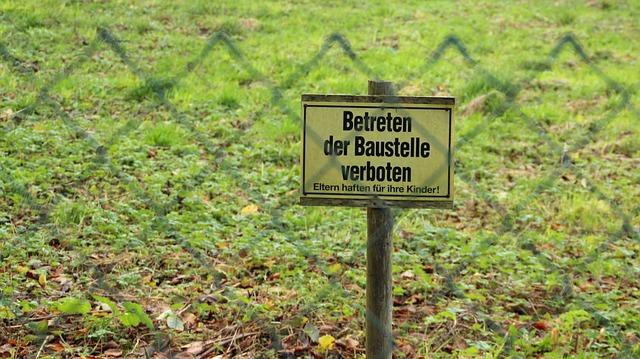 Schild hinter Zaun Betreten der Baustelle verboten