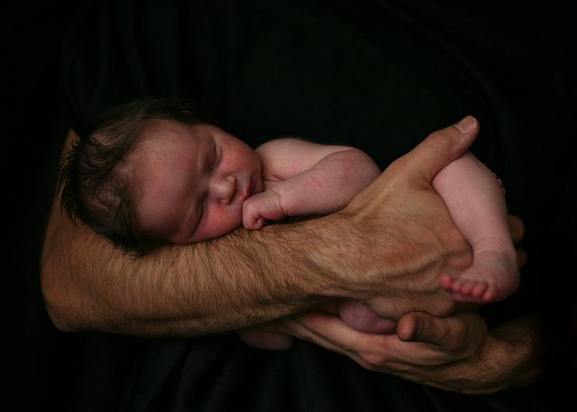 Nacktes Baby in Papas Armen