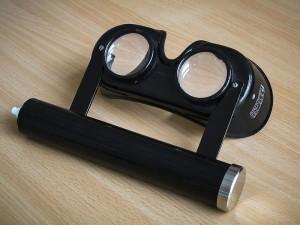 Frenzelbrille, der zylinderförmige Teil enthält die Batterien zur Stromversorgung der Lichtquelle in der Brille.