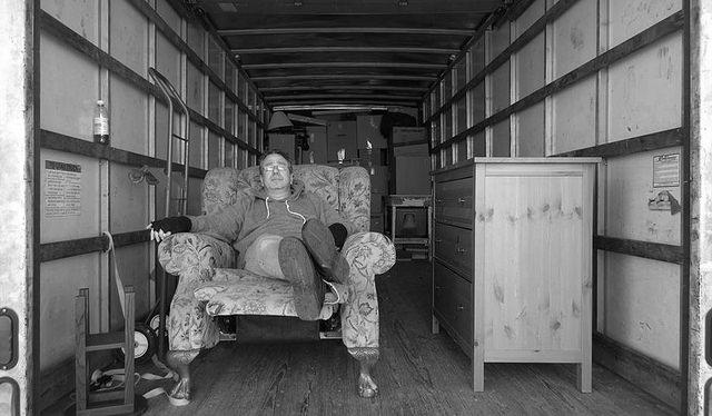 mann-sitzt-auf-sessel-im-umzugswagen