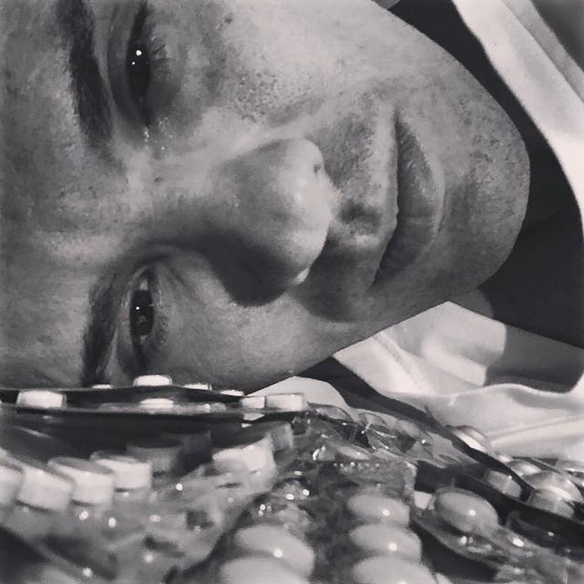trauriger Mann mit Tabletten im Vordergrund